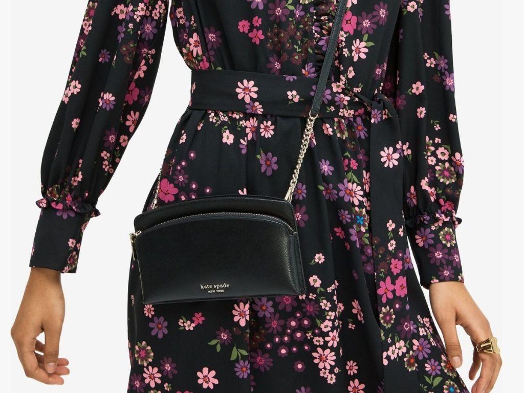 woman in flower dress wearing black kate spade crossbody bag
