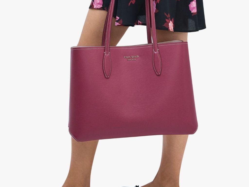 woman holding maroon kate spade bag
