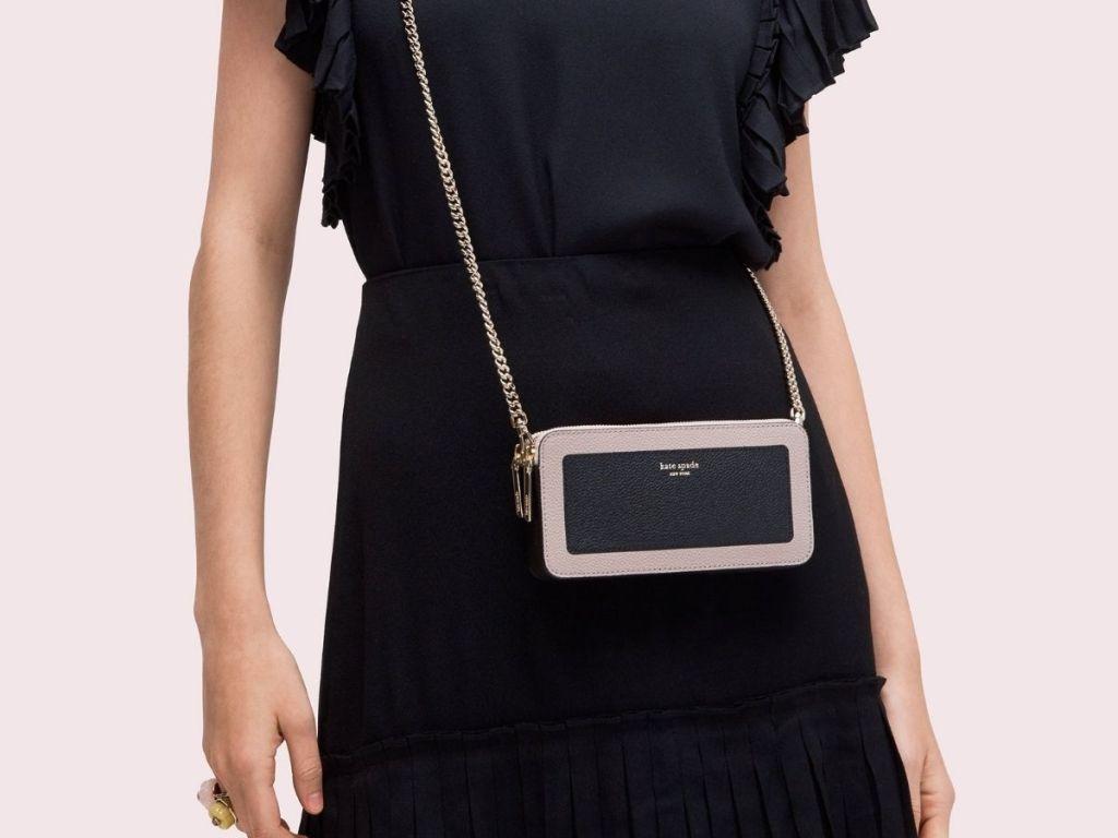 woman wearing pink and black kate spade crossbody bag