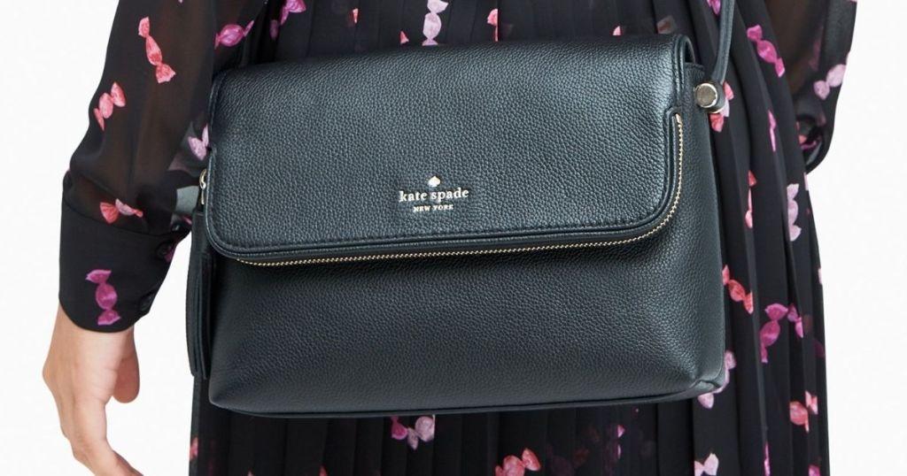 woman in black dress wearing Kate Spade black crossbody bag