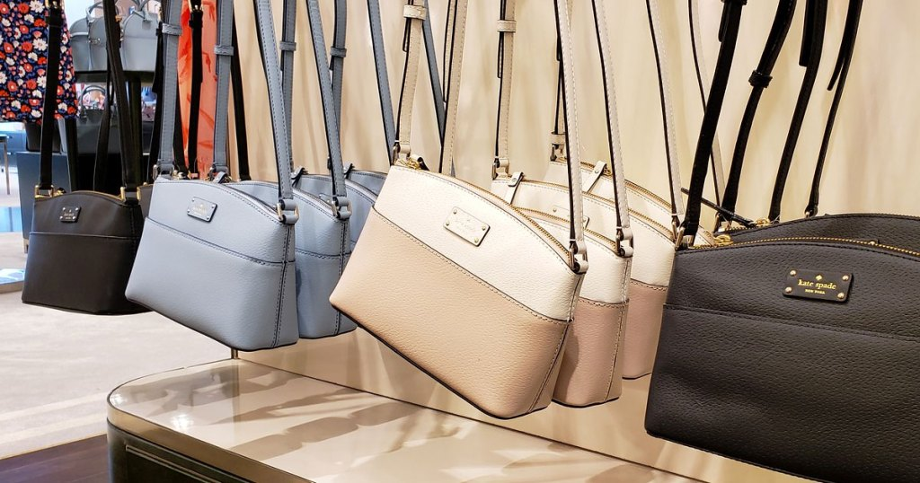 various colors of kate spade crossbody bags on display at store