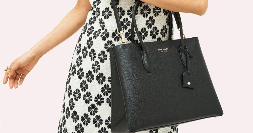 Wanita berbaju floral putih dan hitam dengan tas sekop kulit hitam di lengannya