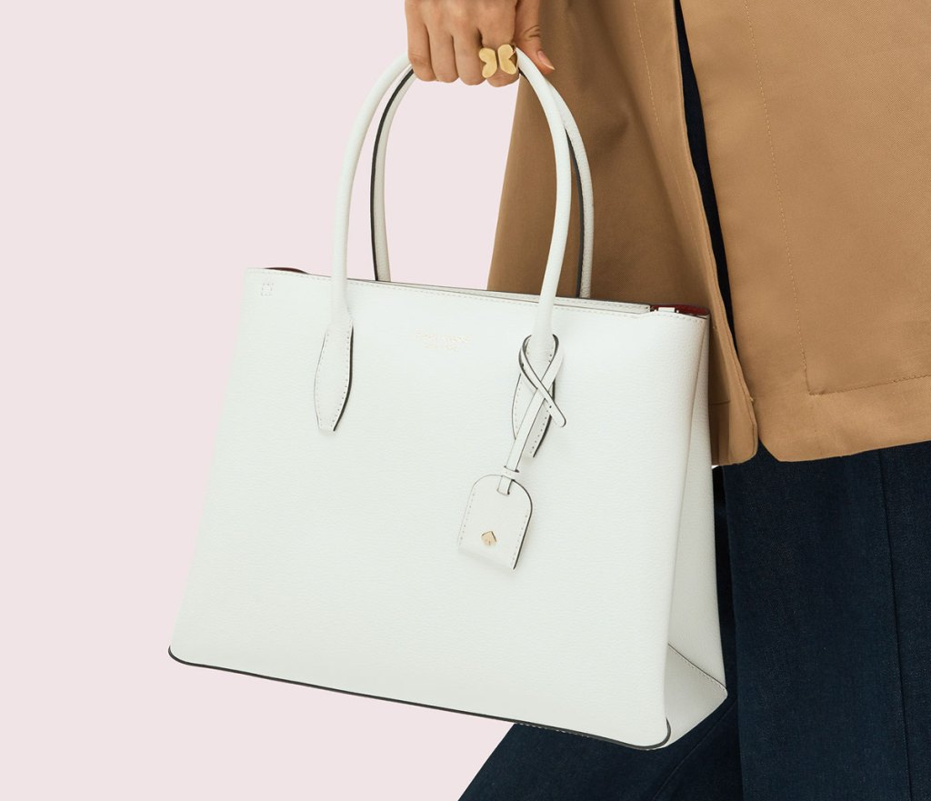 woman in tan coat with black pants holding white leather kate spade bag