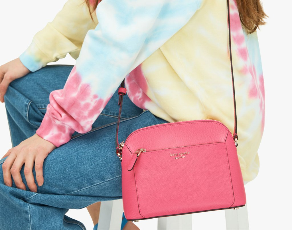woman sitting on white stool wearing jeans and tie-dye sweatshirt with a prink crossbody bag