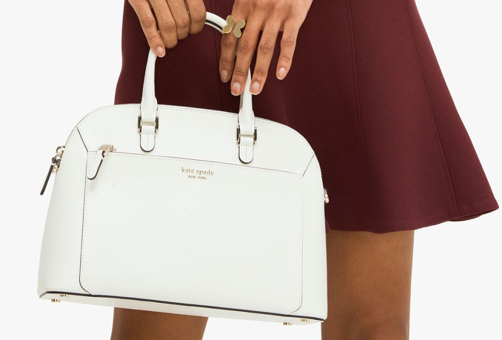 woman in maroon mini skirt holding a white leather kate spade dome shaped purse