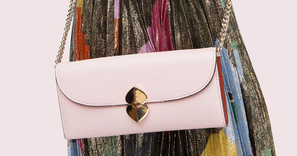 woman in a multi-color dress with a light pink crossbody bag with gold double heart closure and gold chain strap