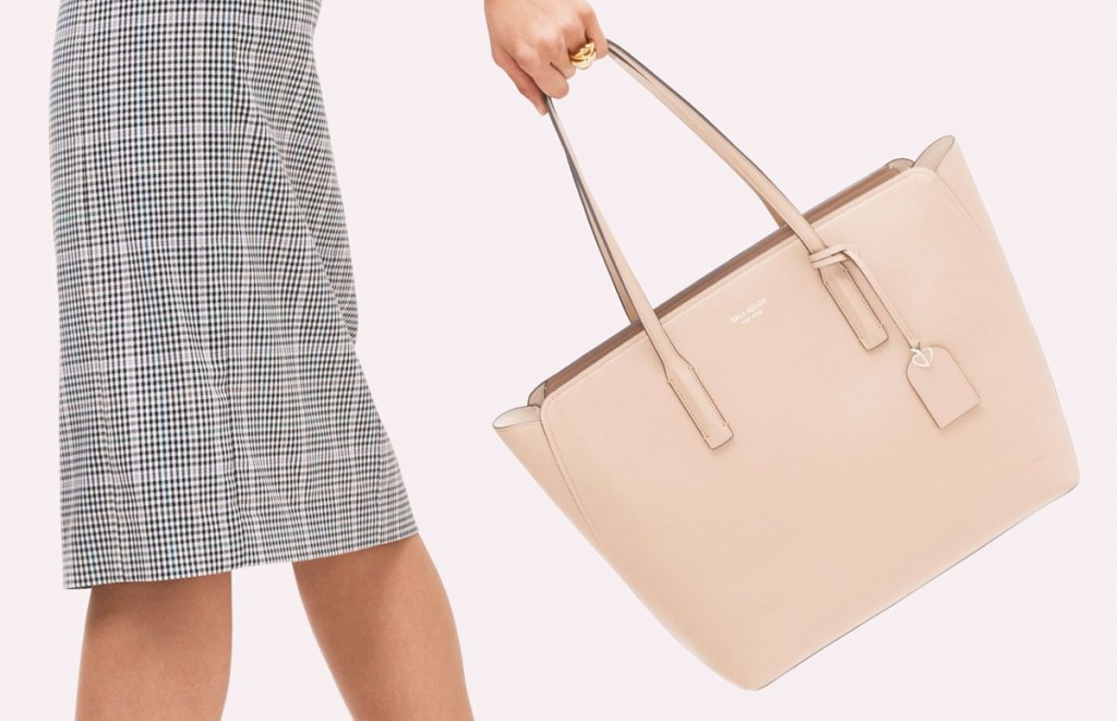 woman in black and white plaid pencil skirt swining a cream colored kate spade tote bag
