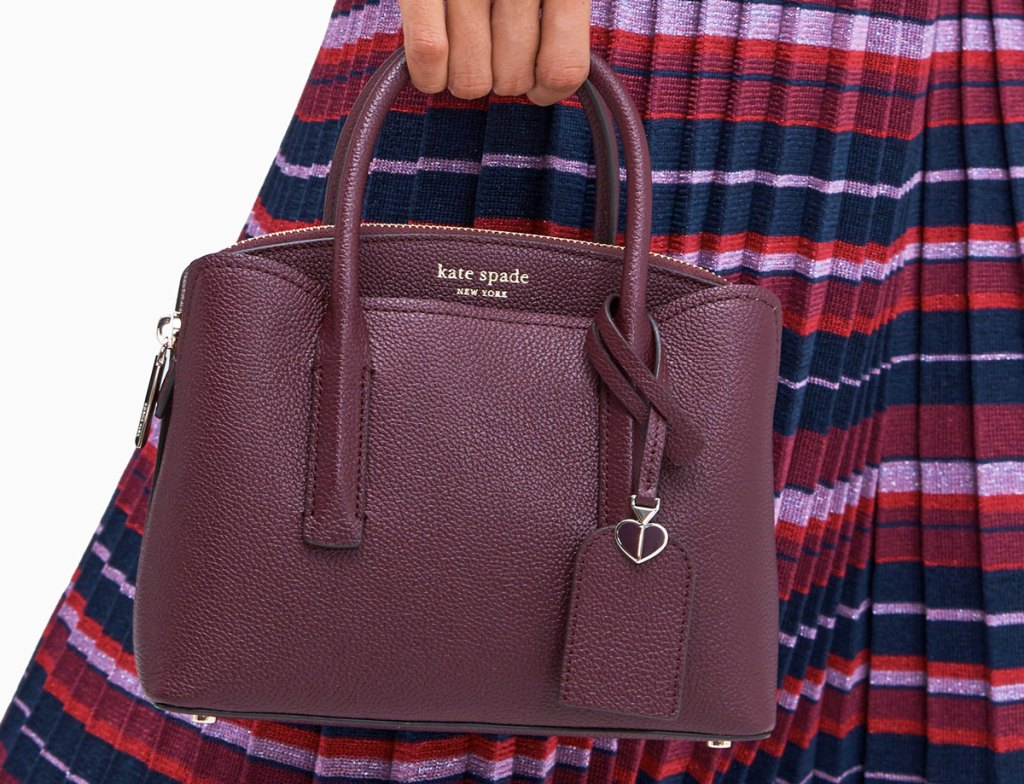 woman in a plated dress holding a wine colored kate spade handbag