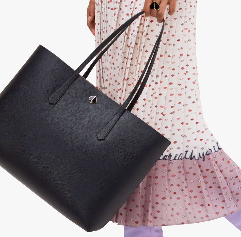 woman in white and pink pleated dress swinging a large black leather kate spade tote bag