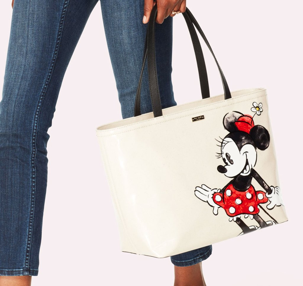 woman wearing skinny jeans and holding white minnie mouse tote bag in her hand