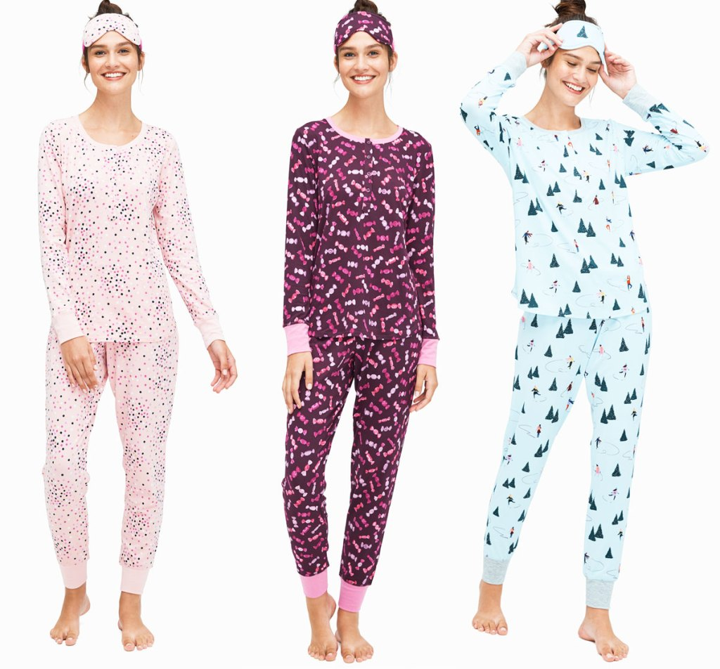 three women wearing printed pajama sets with logger pants, long sleeve henley tops, and matching sleep masks on their heads