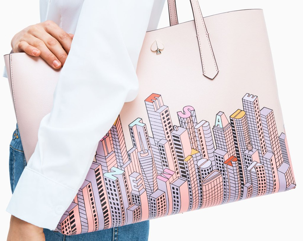 woman in a white long sleeve top with a pale pink kate spade tote bag on her shoulder with new york city skyline print