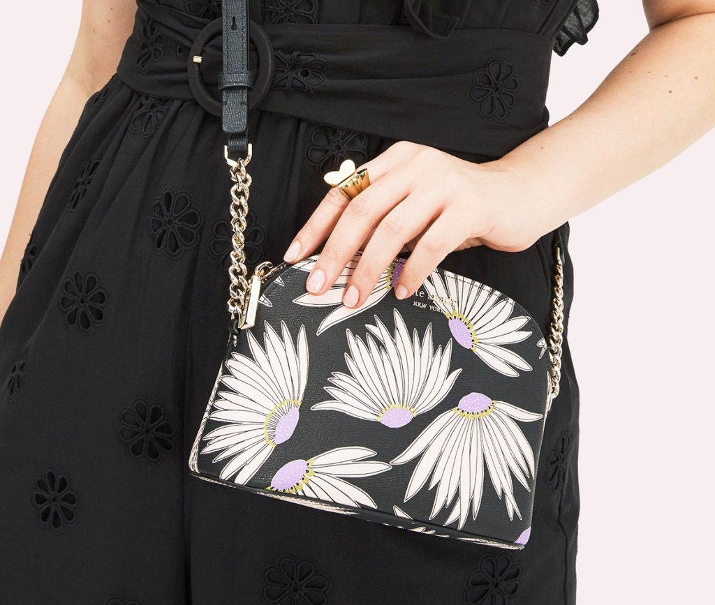 woman in black dress with a dome shaped crossbody with white flower print