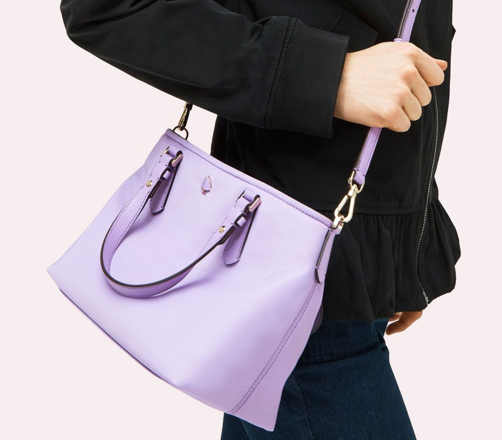 woman in black jacket with a lilac colored kate spade crossbody tote