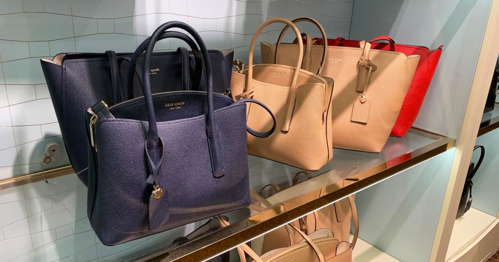 navy blue and tan colored kate spade handbags on glass shelf at store