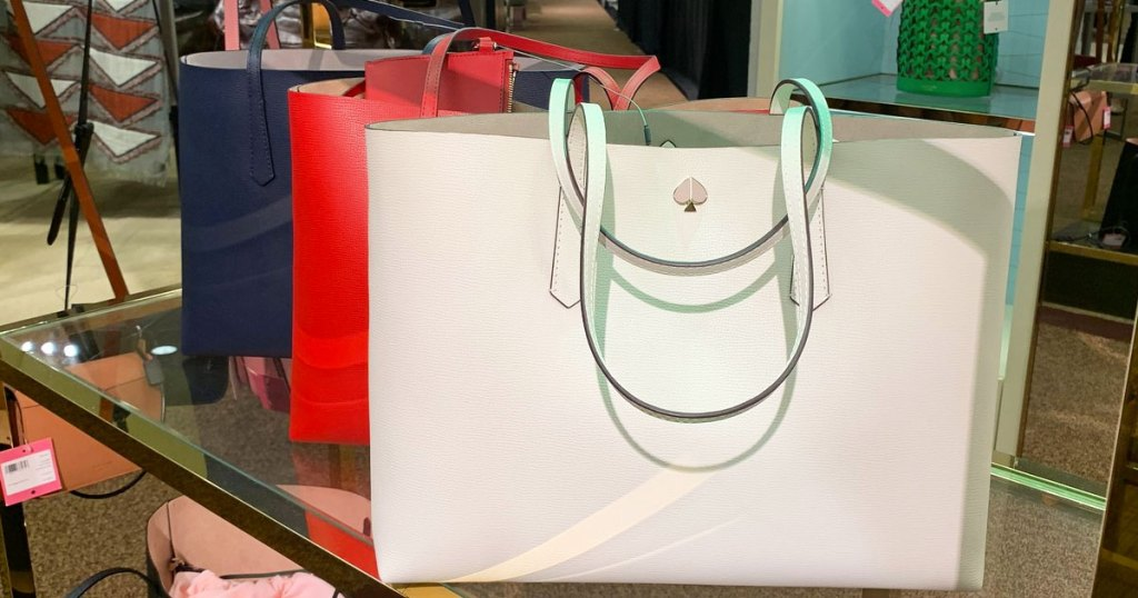 navy blue, red, and white kate spade large leather tote bags on display at store