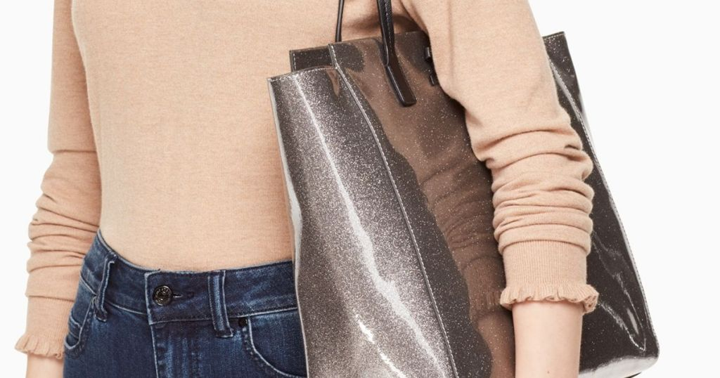 wanita yang membawa tas jinjing Kate Spade