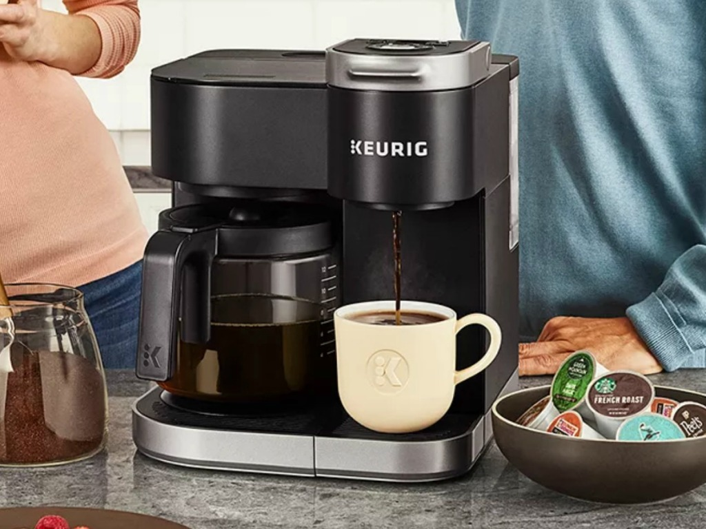 Keurig brewer with coffee mug near family in kitchen