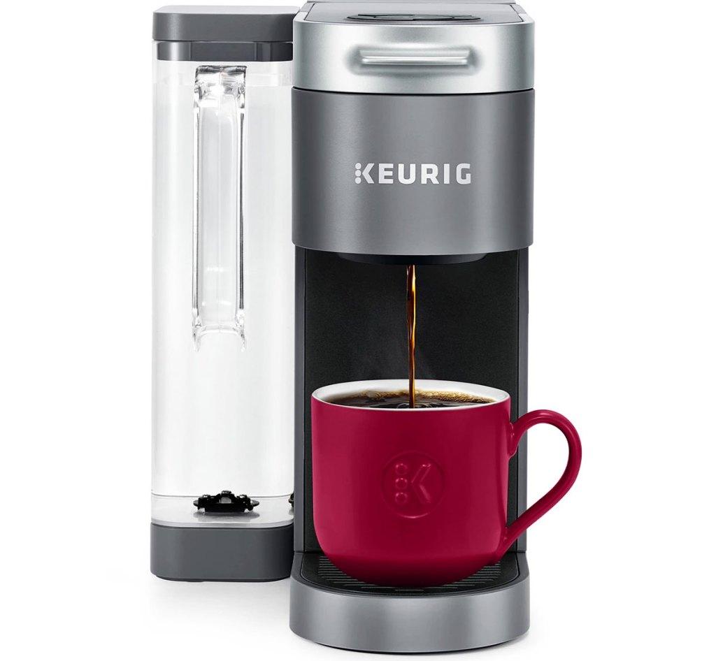 grey keurig coffee maker brewing coffee into a red mug
