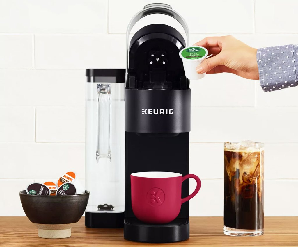 person placing a k-cup into the top of a keurig brewer