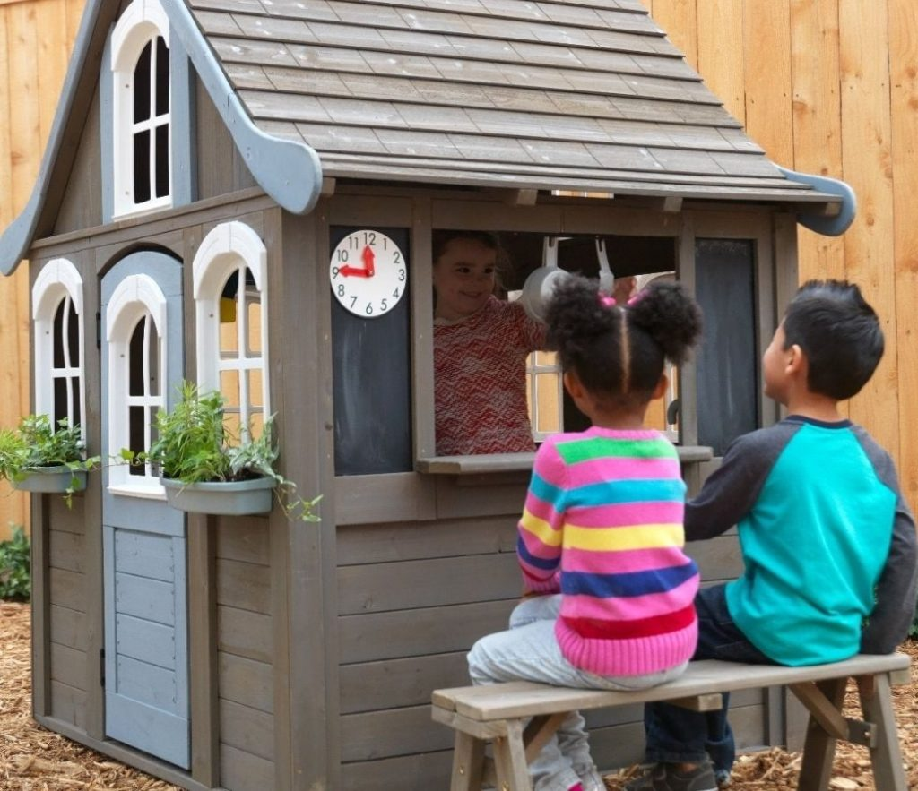 Kids playing in Kidkraft Forestview Wooden Playhouse