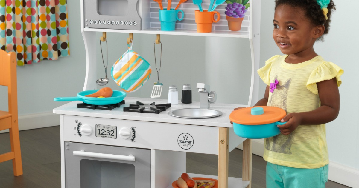 Young girl playing with a wooden kitchen and toy food