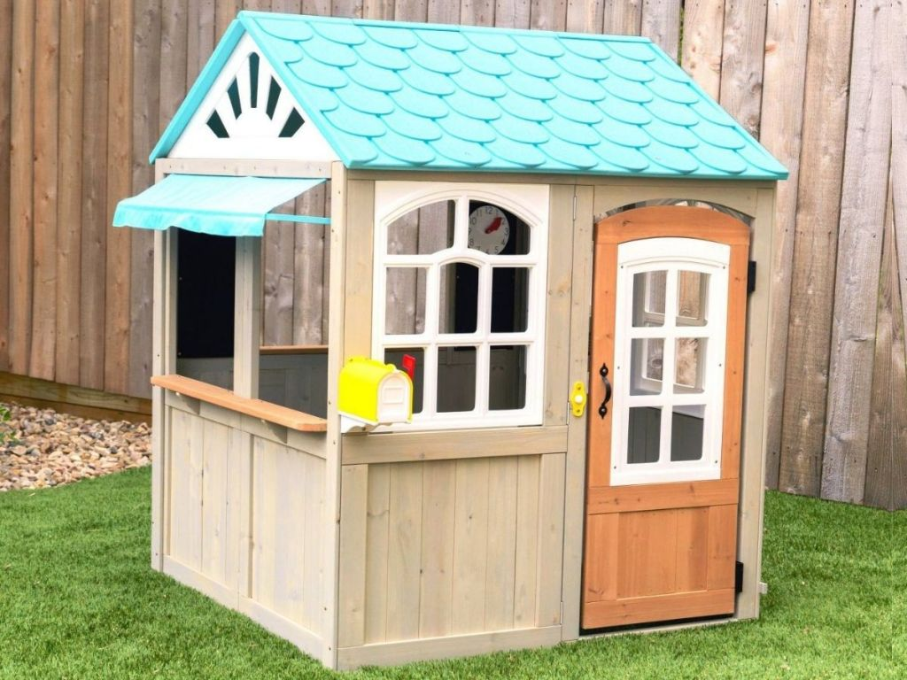 kids playhouse outside with fence in background
