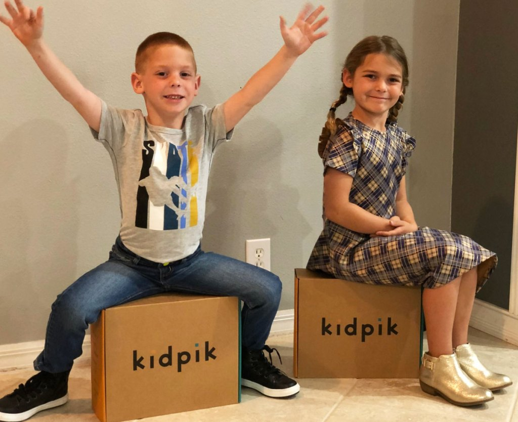 boy and girl sitting on top of kidpik boxes
