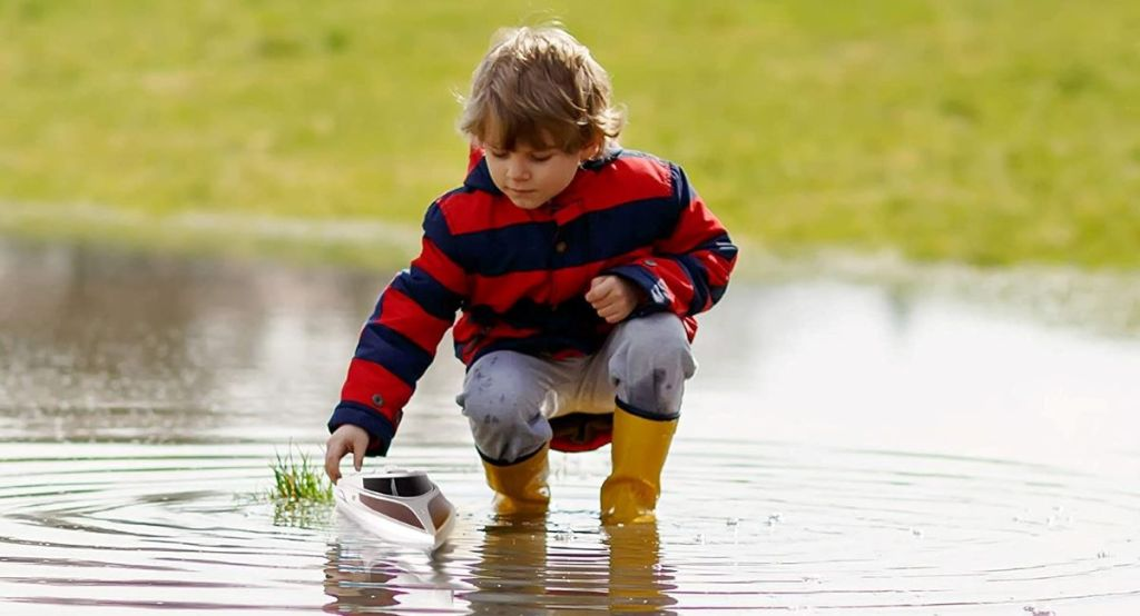 boy playing with a remote control boat