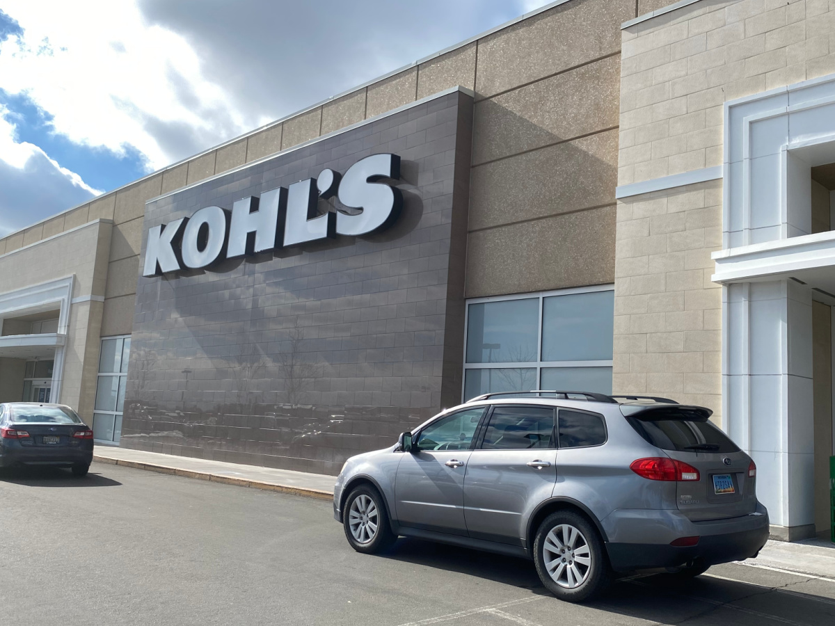 car parked outside a kohl's store next to a curb