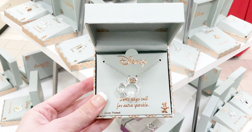 woman holding up silver minnie mouse necklace in silver jewelry box