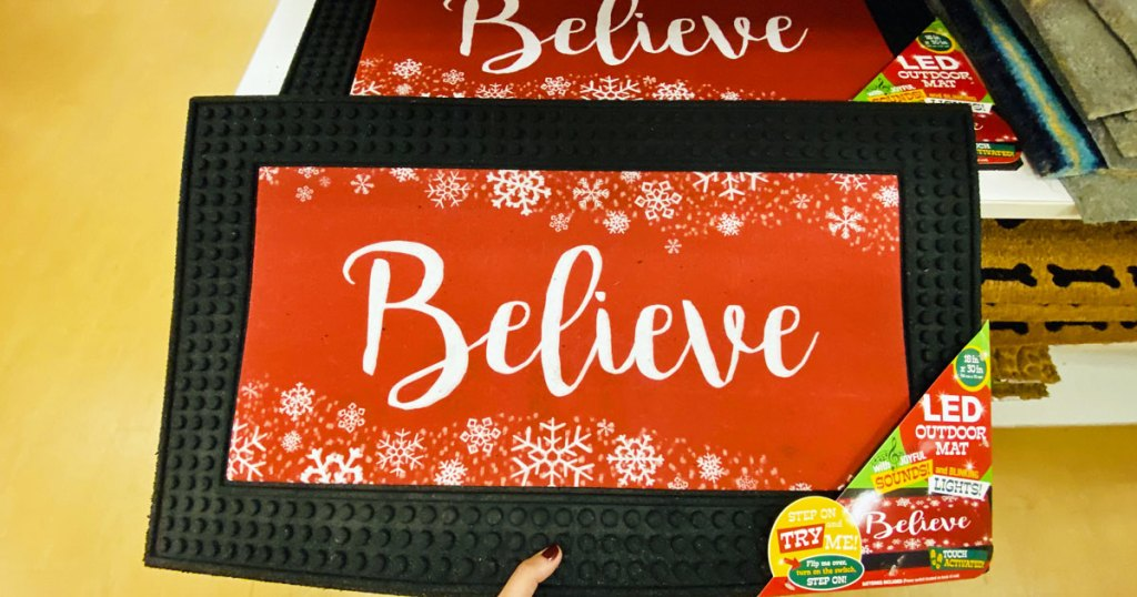 woman holding a red doormat with black boarder with white snowflakes and says believe in white text