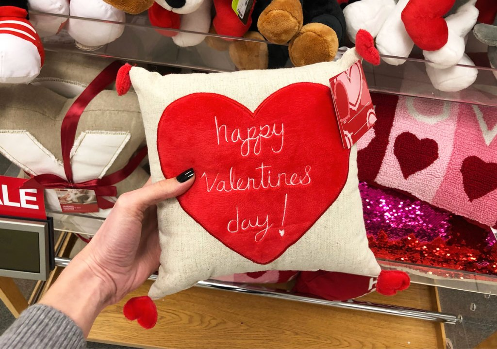 woman holding up throw pillow with heart that says happy valentine's day