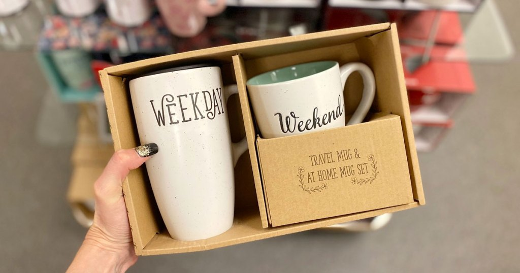 "woman holding up boxed coffee mug set with large mug that says ""weekday"" and smaller mug that says ""weekend"""