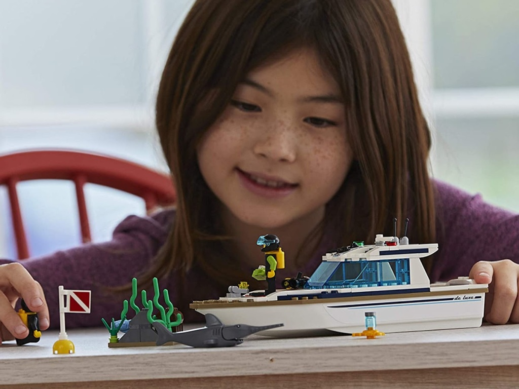 girl playing with yacht building kit