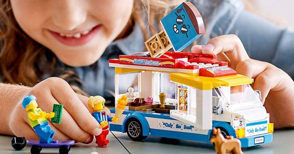 kid playing with a LEGO truck
