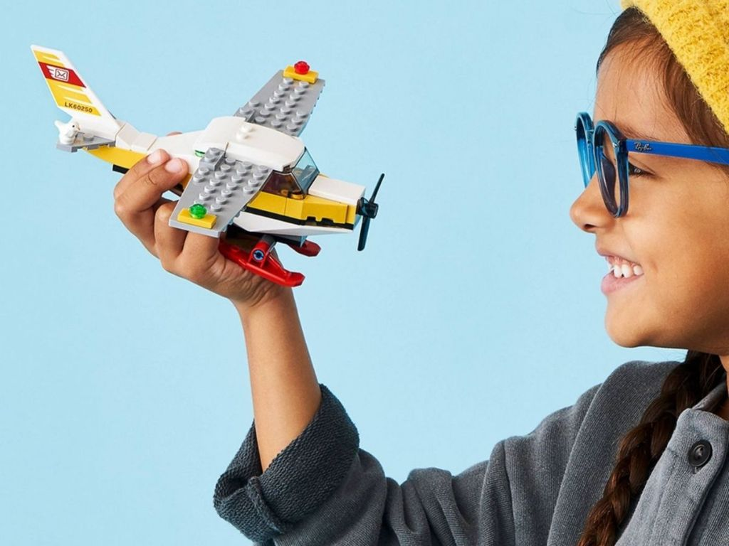 child holding a lego plane