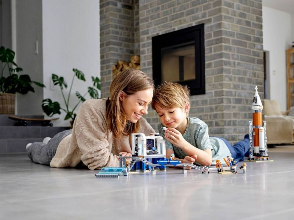 woman and child laying on the floor playing with a lego rocket building set