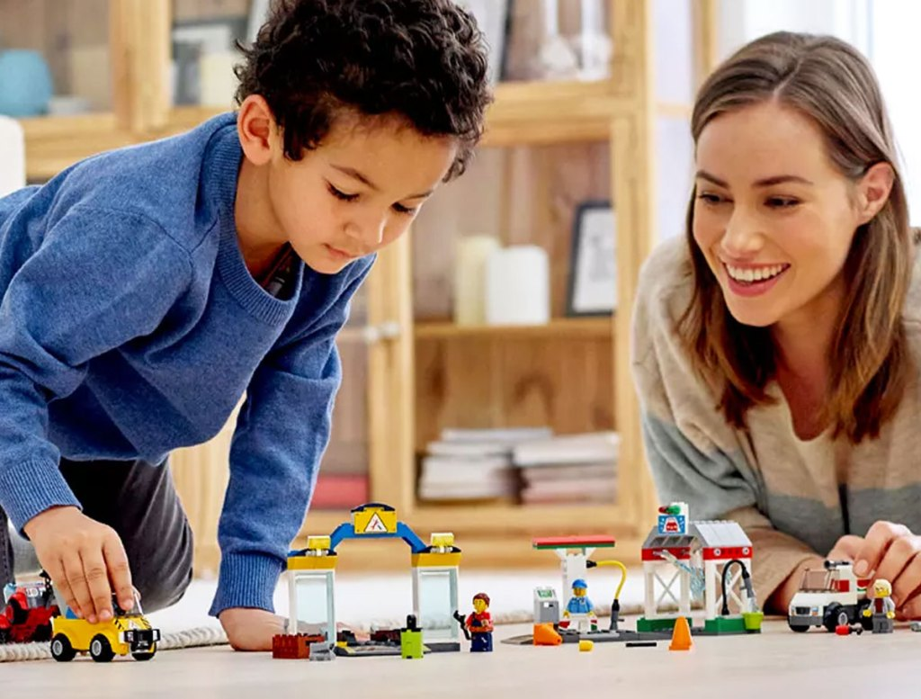 boy and mom playing with a lego city car set on the floor