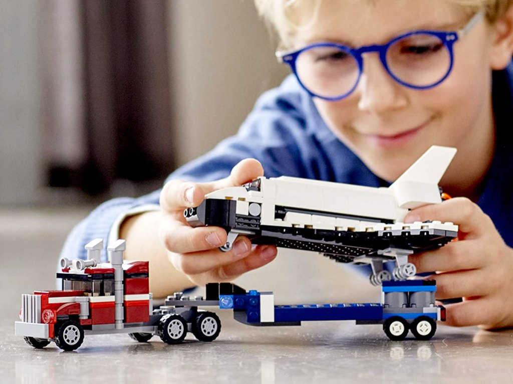 boy with blue glasses playing with a lego semi truck carrying the space shuttle