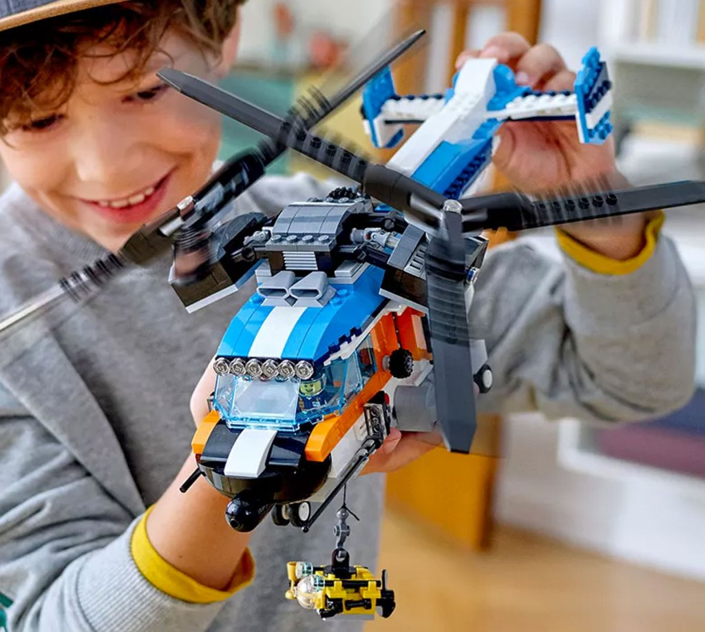 boy in grey sweatshirt holding up a blue and black lego helicopter