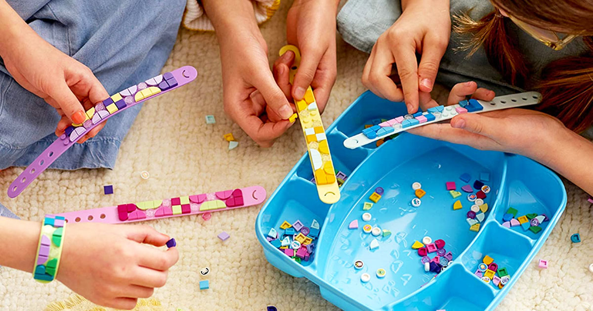 kids sitting on floor decorating lego dots bracelets with pieces inside a blue storage case