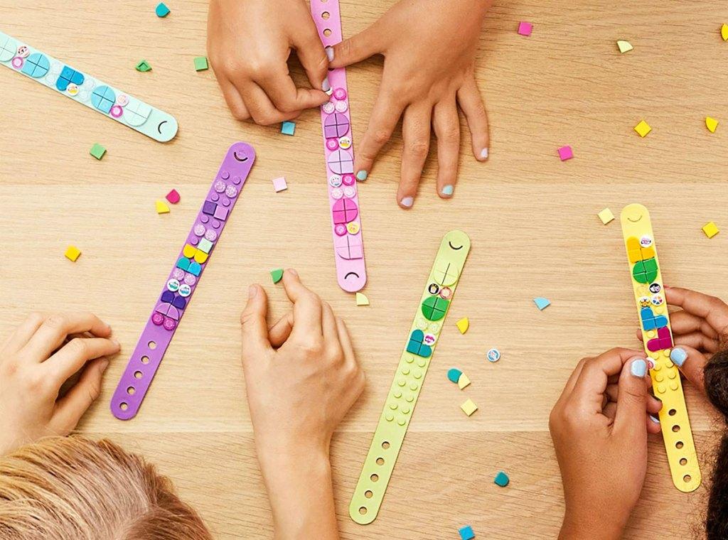 kids decorating lego dots bracelets on a wood table
