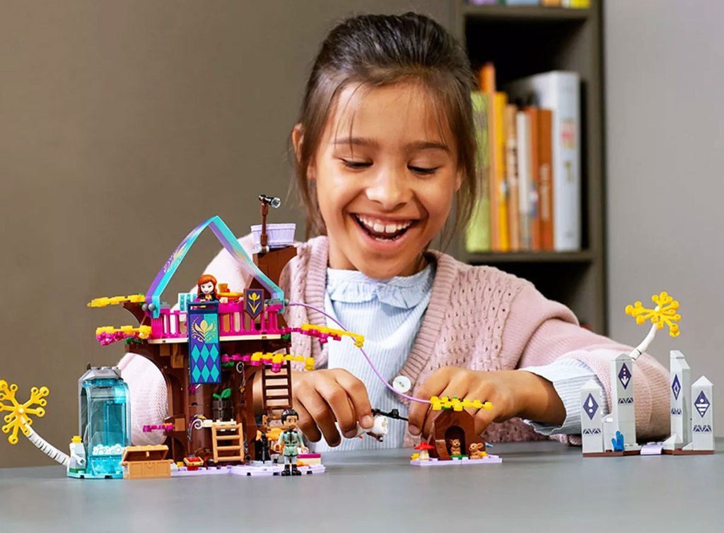 girl with black hair play with lego disney frozen treehouse set on a grey table