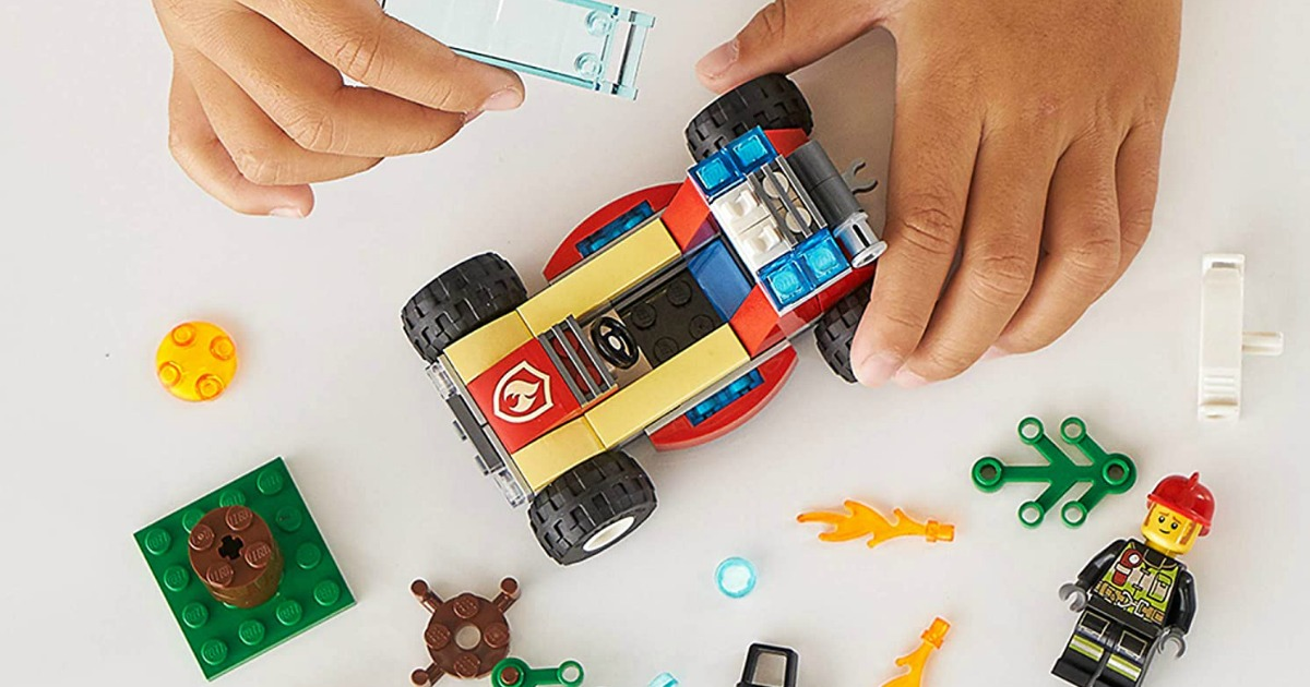 Kids hands holding a buildable LEGO cart
