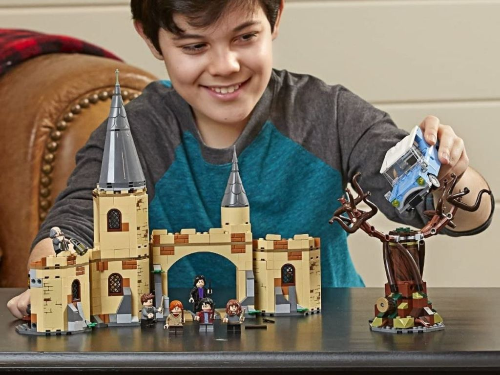 boy playing with Harry Potter LEGO set