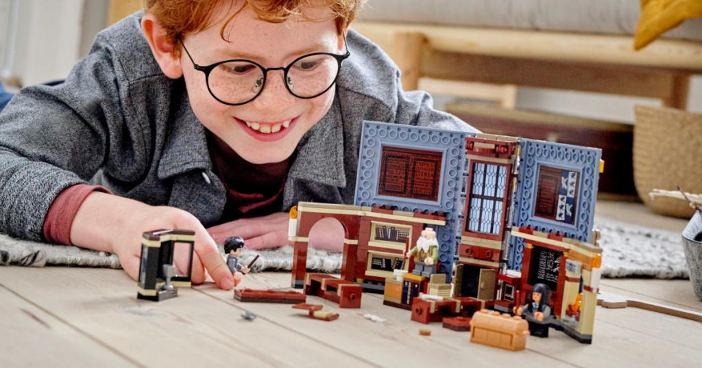 boy on floor playing with Harry Potter LEGO set