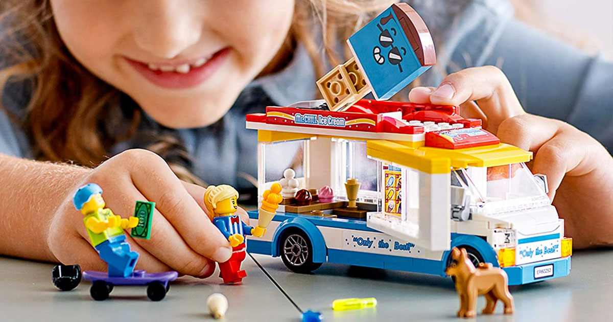 girl playing with a lego ice cream truck with with minifigures holding ice cream cones