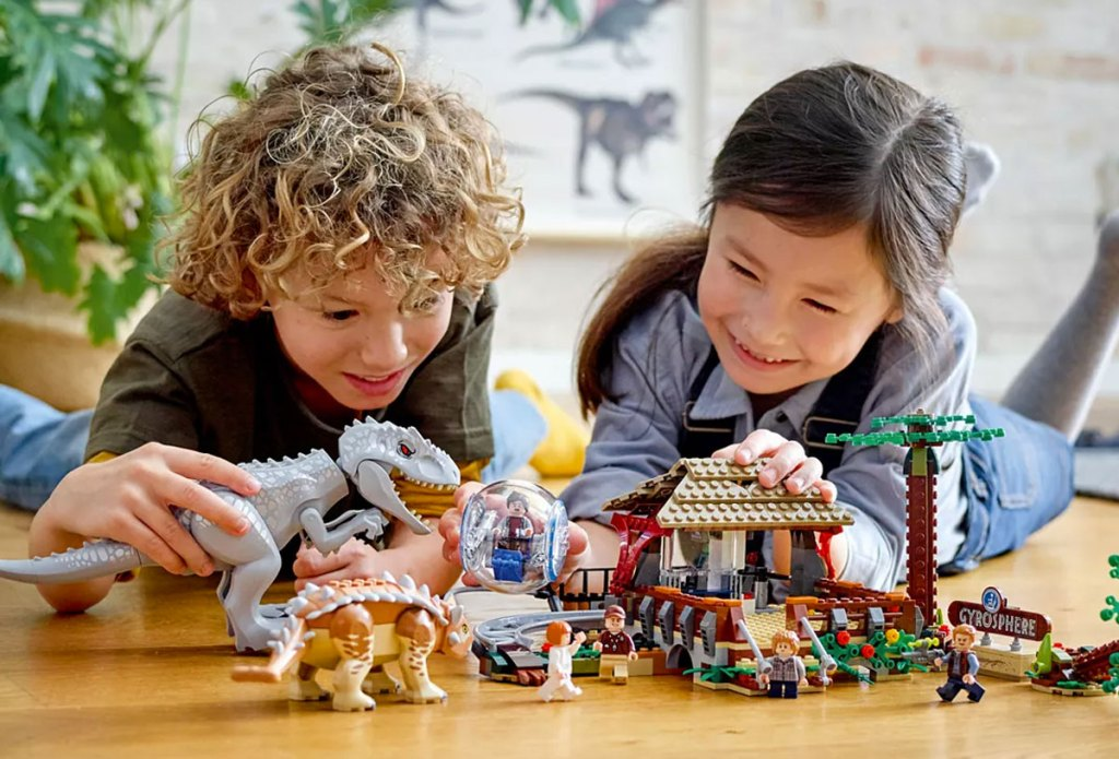 two kids laying on hardwood floor playing with jurassic world lego set