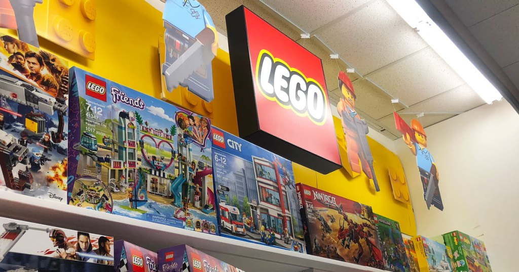 red lego sign and minifigures hanging above lego display shelves at kohl's